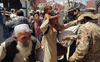 TOPSHOT - Pakistani soldiers (R) check stranded Afghan nationals at the Pakistan-Afghanistan border crossing point in Chaman on August 13, 2021, after the Taliban took control of the Afghan border town in a rapid offensive across the country. (Photo by - / AFP) (Photo by -/AFP via Getty Images)