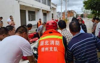 Soccorritori usano una barca per evacuare i residenti da un'area colpita dall'alluvione a Suizhou, nella provincia cinese di Hebei