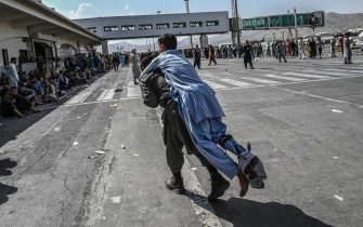 TOPSHOT - A volunteer carries an injured man as other people can be seen waiting at the Kabul airport in Kabul on August 16, 2021, after a stunningly swift end to Afghanistan's 20-year war, as thousands of people mobbed the city's airport trying to flee the group's feared hardline brand of Islamist rule. (Photo by Wakil Kohsar / AFP) (Photo by WAKIL KOHSAR/AFP via Getty Images)