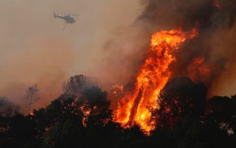 epa09418196 A firefghting helicopter battles a wildfire around the village of Cannet des Maures, France, 17 August 2021. Firefighters are battling wildfires and thousands of residents are evacuated in the area near St. Tropez.  EPA/GUILLAUME HORCAJUELO