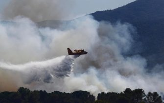 epa09418076 A firefighting aircraft drops water at the scene of a forest fire in the town of Gonfaron, near Saint-Tropez, France, 17 August 2021. Firefighters are battling wildfires and thousands of residents are evacuated in the area near St. Tropez.  EPA/GUILLAUME HORCAJUELO