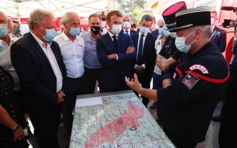 epa09418066 French President Emmanuel Macron (C), French Interior Minister Gerald Darmanin (R) and President of Paca regional council Renaud Muselier (L) visit the SDIS (Departmental fire and rescue service) and firefighters headquarter in Le Luc, near Saint-Tropez, France. Firefighters are battling wildfires and thousands of residents are evacuated in the area near St. Tropez.  EPA/GUILLAUME HORCAJUELO/POOL