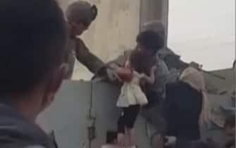 Una madre lancia il figlio oltre il filo spinato all'aeroporto di Kabul
