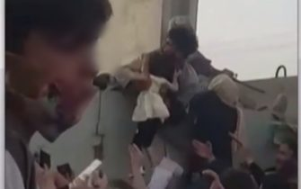 Un bambino viene lanciato oltre il filo spinato all'aeroporto di Kabul
