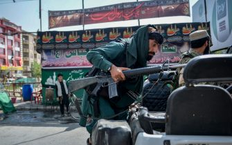 A Taliban fighter clibms up on a vehicle along a makeshift tent where the Shiite Muslims distribute sherbet to people during the Ashura procession which is held to mark the death of Imam Hussein, the grandson of Prophet Mohammad, along a road in Kabul on August 19, 2021, amid the Taliban's military takeover of Afghanistan. (Photo by HOSHANG HASHIMI / AFP) (Photo by HOSHANG HASHIMI/AFP via Getty Images)