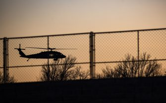 A Blackhawk helicopter flies behind a recently constructed security fence on the National Mall in Washington, D.C., U.S., on Tuesday, Jan. 12, 2021. House Democrats Monday introduced a resolution to impeach President Trumpfor a second time, setting up a vote this week unless Vice PresidentMike Penceuses his constitutional authority to remove the president. Photographer: Samuel Corum/Bloomberg