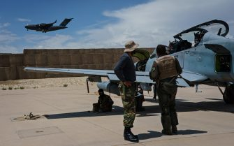 KANDAHAR, AFGHANISTAN -- MAY 6, 2021: With a U.S. Air Force transport plane in the background, an Afghan A-29 pilot confers with his maintainers after a mission, at Kandahar Airbase in Kandahar, Afghanistan, Thursday, May 6, 2021. The Afghan Air Force, which the U.S. and its partners has nurtured to the tune of $8.5 billion since 2010, is now the governmentÕs spearhead in its fight against the Taliban. Since May 1, the original deadline for the U.S. withdrawal, the Taliban have overpowered government troops to take at least 23 districts to date, according to local media outlets. That has further denied Afghan security forces the use of roads, meaning all logistical support to the thousands of outposts and checkpoints Ñ including re-supplies of ammunition and food, medical evacuations or personnel rotation Ñ must be done by air.  (MARCUS YAM / LOS ANGELES TIMES)