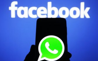 In this photo illustration a WhatsApp logo seen on a smartphone screen and the Facebook logo in the background. In January 2021, WhatsApp announced a new Privacy Policy that will allow WhatsApp to share data with Facebook, and users will be to accept the new policy by 8 February 2021, or stop using the app, reportedly by media. (Photo by Pavlo Gonchar / SOPA Images/Sipa USA)