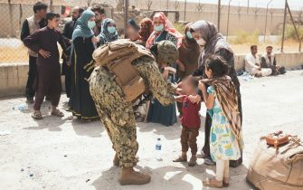 A US soldier checks a child arriving at an Evacuate Control Center at Hamid Karzai International Airport, in Kabul, Afghanistan, on August 19, 2021, in the days following the fall of Kabul to Taliban movement, amid chaos and panic scenes at the capital's airport. Photo by CENTCOM-Balkis Press/ABACAPRESS.COM