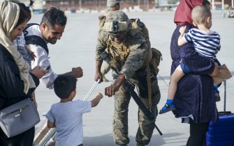 No UK - No US: A United States Marine assigned to 24th Marine Expeditionary Unit fists bumps a child evacuee during a military drawdown at Hamid Karzai International Airport, Afghanistan, August 18, 2021. US service members are assisting the US Department of State with an orderly drawdown of designated personnel in Afghanistan. Mandatory Credit: Nicholas Guevara / US Marine Corps via CNP/AdMedia//Z-ADMEDIA_adm_082021_AghanRelease_CNP_011/2108212202/Credit:CNP/AdMedia/SIPA/2108212203