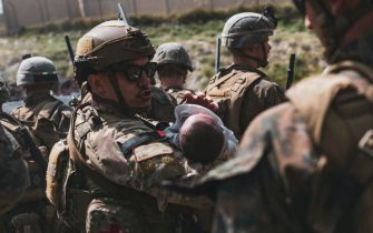 A US soldier calms an infant during an evacuation at Hamid Karzai International Airport, Kabul, Afghanistan, on August 20, 2021, in the days following the fall of Kabul to Taliban movement, amid chaos and panic scenes at the capital's airport. Photo by CENTCOM-Balkis Press/ABACAPRESS.COM
