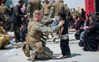 No UK - No US: A United States Marine with the 24th Marine Expeditionary Unit (MEU) provides fresh water to a child during an evacuation at Hamid Karzai International Airport, Kabul, Afghanistan, August 20, 2021. US service members are assisting the US Department of State with an orderly drawdown of designated personnel in Afghanistan.  Mandatory Credit: Samuel Ruiz / US Marine Corps via CNP/AdMedia//Z-ADMEDIA_adm_082021_AghanRelease_CNP_013/2108212206/Credit:CNP/AdMedia/SIPA/2108212207