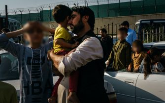 KABUL, AFGHANISTAN -- AUGUST 19, 2021: A father rests his head on his childÕs face as his elder son puts both his hands on his head in despair on the road to the military entrance of the airport for evacuations, in Kabul, Afghanistan, Thursday, Aug. 19, 2021.Here Afghans are made to wait behind the first Taliban checkpoint, before bringing their worldly possessions one can only carry in both hands to the military gate for evacuations out of the country. A few hundred people congregate there listening to spotty announcements from a skinny Taliban fighter with neck-length hair standing on an elevated platform, wearing a surgical mask for covid19 prevention, but barely covering his mouth. On his right hand a cold water bottle. On his left hand a semi-automatic pistol and a walkie talkie radio that he occasionally waves to the crowd to get their attention. The Taliban fighter with the pistol announces that they will call out names of countries and people with approval for flights to those countries will be allowed to pass. (MARCUS YAM / LOS ANGELES TIMES)