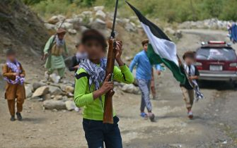 Children of local Afghan residents carrying hunting rifles and a flag walk through a road in Bandejoy area of Dara district in Panjshir province on August 21, 2021, days after the Taliban stunning takeover of Afghanistan. (Photo by Ahmad SAHEL ARMAN / AFP) (Photo by AHMAD SAHEL ARMAN/AFP via Getty Images)