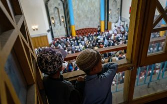 KABUL, AFGHANISTAN -- AUGUST 20, 2021: Two boys listen to Mohammad Shafiq Khatib giving a religious sermon at the Pul-I-Khishti Mosque in Kabul, Afghanistan, Friday, Aug. 20, 2021. (MARCUS YAM / LOS ANGELES TIMES)
