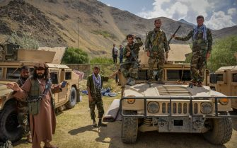 Afghan armed men supporting the Afghan security forces against the Taliban stand with their weapons and Humvee vehicles at Parakh area in Bazarak, Panjshir province on August 19, 2021. (Photo by Ahmad SAHEL ARMAN / AFP) (Photo by AHMAD SAHEL ARMAN/AFP via Getty Images)