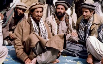 """SHO-E-SALIM, AFGHANISTAN:  File photo taken 12 October 1990 in Sho-E-Salim of Afghan opposition commander Ahmad Shah Masood (2ndL) talking with aides. French Foreign Minister Hubert Vedrine said 14 September 2001 that """"it appears to be confirmed that commander Ahmad Shah Masood, the head of the Afghan opposition, has died"""". AFP PHOTO (Photo credit should read AFP via Getty Images)"""