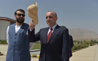 Vice President of Afghanistan Amrullah Saleh (R) gestures holding his cap as he stands along with National Security Adviser of Afghanistan Hamdullah Mohib as they wait for the arrival of Afghanistan's President Ashraf Ghani (not pictured) prior to a meeting at the  Afghan Parliament house in Kabul on August 2, 2021. (Photo by Wakil KOHSAR / AFP) (Photo by WAKIL KOHSAR/AFP via Getty Images)