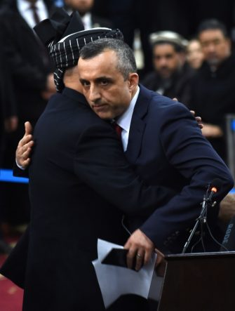 Afghan President Ashraf Ghani (L) hugs his first vice-presidential candidate Amrullah Saleh (R) after arriving at the Independent Electoral Commission office in Kabul on January 20, 2019. - President Ashraf Ghani on January 20 formally registered as a candidate for Afghanistan's delayed presidential election, setting up a rematch with Chief Executive Abdullah Abdullah in the July ballot. (Photo by WAKIL KOHSAR / AFP)        (Photo credit should read WAKIL KOHSAR/AFP via Getty Images)