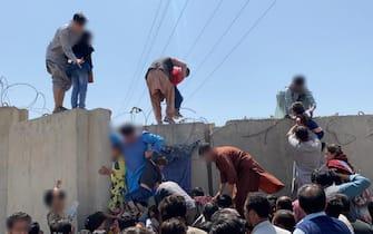 Cittadini afghani provano a scappare scavalcando un muro