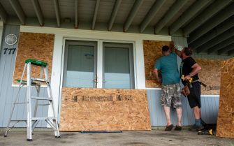 Members of the Edelweiss construction crew work fast to protect costal homes by barricading their windows and doors with plywood sheets before Hurricane Henri hits the beach front area in New London, Connecticut on August 21, 2021. - A swath of the US East Coast, including New York City, was under alert Saturday, as storm Henri was upgraded to what could be the first hurricane in 30 years to hit New England. (Photo by JOSEPH PREZIOSO / AFP) (Photo by JOSEPH PREZIOSO/AFP via Getty Images)