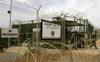 GUANTANAMO BAY, CUBA - AUGUST 23:  A Soldier walks through a gate at Camp Delta at Guantanamo Naval Base August 23, 2004 in Guantanamo, Cuba. On August 24, preliminary hearings will begin for four suspected Al Qaeda associates charged by the U.S. with war crimes as they appear before a commission of five military officers.  (Photo by Mark Wilson/Getty Images)