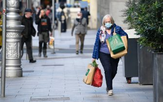 epa08762242 A woman wearing a face mask carries shopping in Dublin City, Ireland, 21 October 2020. The Irish government has announced level 5 restrictions for the whole country from 22 October 2020, which will see all unessential retail shops, restaurants, and bars close for six weeks. Cases of COVID-19 have been rising in Ireland for the past number of weeks.  EPA/AIDAN CRAWLEY