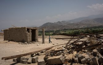 SHADAL BAZAAR, AFGHANISTAN - JULY 15: A boy walks through buildings damaged from fighting on July 15, 2017 in Shadal Bazaar, Afghanistan. People are slowly returning to the recently liberated area, which had previously been a front line of fighting against the Islamic State of Iraq and Syria - Khorasan (ISIS-K) in Achin District of Nangarhar Province. (Photo by Andrew Renneisen/Getty Images)