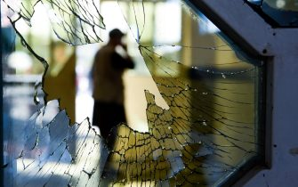 TOPSHOT - A man is seen through a broken window of a wedding hall after a deadly bomb blast in Kabul on August 18, 2019. - More than 60 people were killed and scores wounded in an explosion targeting a wedding in the Afghan capital, authorities said on August 18, the deadliest attack in Kabul in recent months. (Photo by Wakil KOHSAR / AFP)        (Photo credit should read WAKIL KOHSAR/AFP via Getty Images)