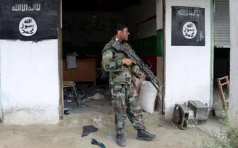 Un soldato afghano con bandiere dell'Isis alle sue spalle