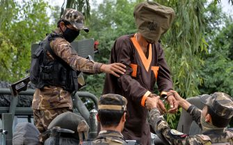 Forces with Afghanistan's National Directorate of Security (NDS) escort an alleged militant as Taliban and Islamic State (IS) fighters are presented to the media in Jalalabad on May 23, 2019. - Afghan security forces have detained seven alleged Taliban and four ISIS militants and seized a suicide vest and ammunition during an operation in Nangarhar province, an official said. (Photo by NOORULLAH SHIRZADA / AFP)        (Photo credit should read NOORULLAH SHIRZADA/AFP via Getty Images)