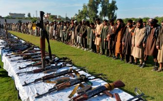 In this photograoh taken on November 17, 2019 members of the Islamic State (IS) group stand alongside their weapons, following they surrender to Afghanistan's government in Jalalabad, capital of Nangarhar Province. - Over 225 Islamic state IS militants including their families 190 women and 208 children were surrendered to government during past two weeks, Afghan security forces lunched a military operation against ISIS in Achin district of Nangarhar province, Nangarhar governor Shamahmod miakhil said. (Photo by NOORULLAH SHIRZADA / AFP) (Photo by NOORULLAH SHIRZADA/AFP via Getty Images)