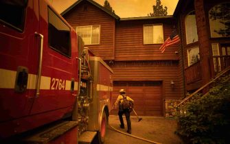 epa09437946 A firefighter grabs his tools under an American Flag while fighting the Caldor Fire in Meyers, California, USA, 30 August 2021. The fire, which has so far burned more than 177,000 acres, caused authorities to issue an evacuation order for residents of the city of South Lake Tahoe.  EPA/CHRISTIAN MONTERROSA
