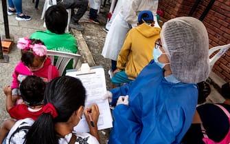 A nurse hands the documentation needed to apply the novel coronavirus vaccine as people in Ragonvalia - Norte de Santander, Colombia get rapid tests and the Jansen Johnson & Johnson novel Coronavirus (COVID-19) on July 7, 2021.