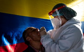 People geting tested for the nover Coronavirus disease with Colombia's national flag on the background during the novel coronavirus (COVID-19) pandemic PCR testing in Hernan, Norte de Santander - Colombia on July 6, 2021.
