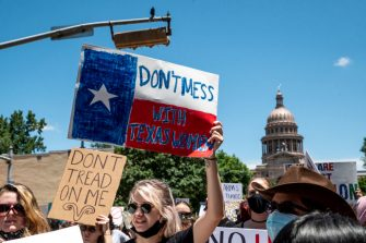 AUSTIN, TX - MAY 29: Protesters hold up signs as they march down Congress Ave at a protest outside the Texas state capitol on May 29, 2021 in Austin, Texas. Thousands of protesters came out in response to a new bill outlawing abortions after a fetal heartbeat is detected signed on Wednesday by Texas Governor Greg Abbot. (Photo by Sergio Flores/Getty Images)