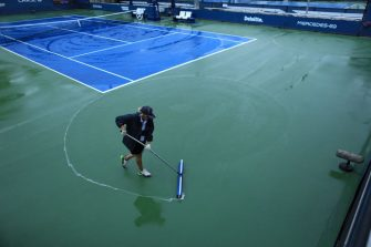 TOPSHOT - Court staff clean the rain off the courts at the USTA Billie Jean King National Tennis Center in New York, on September 1, 2021. - Outside court matches have been postponed as the remnants for Hurricane Ida pass through the region. (Photo by KENA BETANCUR / AFP) (Photo by KENA BETANCUR/AFP via Getty Images)
