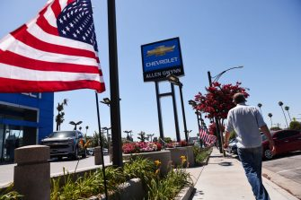 GLENDALE, CALIFORNIA - AUGUST 04: A person walks past a Chevrolet dealership on August 4, 2021 in Glendale, California. In spite of a computer chip shortage, General Motors (GM) posted a $2.8 billion net profit in the second quarter. (Photo by Mario Tama/Getty Images)