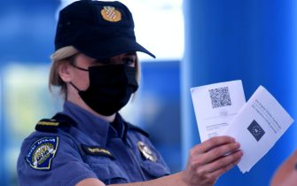 epa09242735 A Police officer holds a COVID-19 Green passport at the Bregana border between Croatia and Slovenia, 02 June 2021. From 02 June 2021, Croatia give to its citizens COVID-19 passports and also check other EU countries citizens passport with QR codes. The first tourists start to come to the Croatian coast mostly from Czech Republic, Slovenia, Austria, Germany and Hungary.  EPA/ANTONIO BAT