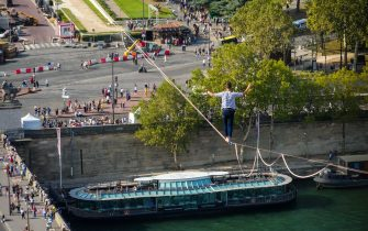 PARIS, FRANCE - SEPTEMBER 18: Tightrope walker Nathan Paulin traverses a slackline between the Eiffel Tower and the Trocadero Square, on September 18, 2021 in Paris, France. The 670 meter walk across the River Seine, along a slackline between the first level of the Eiffel Tower and Paris' Trocadero Square, is a 30 minutes performance during the European Heritage Days. (Photo by Edward Berthelot/Getty Images)