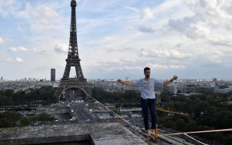 French highliner Nathan Paulin performs on a 70-metre-high slackline spanning 670 metres between the Eiffel Tower and the Theatre National de Chaillot, as part of the 38th European Heritage Days and the launch of the Cultural Olympiad in Paris, on September 18, 2021. - From the first floor of the Eiffel Tower to the Theatre National de Chaillot, the performance is the longest highline crossing in an urban environment. (Photo by Alain JOCARD / POOL / AFP) (Photo by ALAIN JOCARD/POOL/AFP via Getty Images)