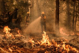A firefighter attempts to extinguish a spot fire off Highway 50 during the Caldor Fire in Meyers, U.S., on Tuesday, Aug. 31, 2021. California's Caldor Fire moved closer to a popular alpine tourist destination in Northern California on Monday, prompting officials to order the evacuation of the resort town of South Lake Tahoe. Photographer: David Odisho/Bloomberg via Getty Images