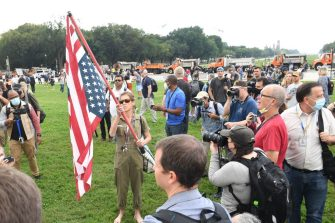 """A demonstrator with an upside-down US flag is surrounded by photographers during the """"Justice for J6"""" rally in Washington, DC, on September 18, 2021, in support of the pro-Trump rioters who ransacked the US Capitol on January 6, 2021. - Washington was on high alert for the rally with security forces better prepared to avoid a repeat of the January 6 attack on the Capitol. US Capitol police said they have no indication of a specific plot associated with the rally, but warned in a news conference there had been """"some threats of violence,"""" with a counter-rally scheduled to take place nearby. (Photo by Eric BARADAT / AFP) (Photo by ERIC BARADAT/AFP via Getty Images)"""
