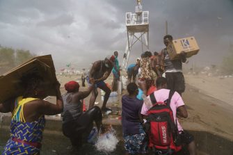TOPSHOT - Migrants, many from Haiti, assist each other as they cross the Rio Grande with supplies near the Del Rio-Acuna Port of Entry in Del Rio, Texas, on September 18, 2021. - The United States said on September 18 that it would ramp up deportation flights for thousands of migrants who flooded into the Texas border city of Del Rio, as authorities scramble to alleviate a burgeoning crisis for President Joe Biden's administration. The migrants who poured into the city, many of them Haitian, were being held in an area controlled by US Customs and Border Protection (CBP) beneath the Del Rio International Bridge, which carries traffic across the Rio Grande river into Mexico. (Photo by PAUL RATJE / AFP) (Photo by PAUL RATJE/AFP via Getty Images)