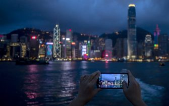 A pedestrian takes a photograph of buildings across Victoria Harbor along the Tsim Sha Tsui waterfront in Hong Kong, China, on Thursday July, 1, 2021. Hong Kong's leader pledged to press ahead with an unprecedented national security crackdown, as the Asian financial center marked a series of fraught anniversaries symbolizing Beijings tightening grip over local affairs. Photographer: Paul Yeung/Bloomberg