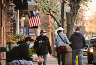 Babylon Village, N.Y.: People wearing masks stroll Main St. in Babylon Village as the sun sets, Wednesday, April 8, 2020. (Photo by Steve Pfost/Newsday RM via Getty Images).