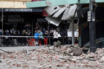 Residents gather near a damaged building in the popular shopping Chappel Street in Melbourne on September 22, 2021, after a 5.9 magnitude earthquake. (Photo by William WEST / AFP) (Photo by WILLIAM WEST/AFP via Getty Images)