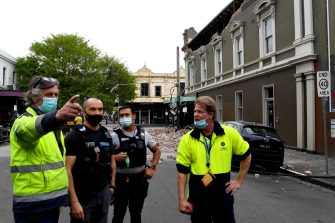 Emergency and rescue officials and police examine the area next to a damaged building in the popular shopping Chapel Street in Melbourne on September 22, 2021, after a 5.9 magnitude earthquake. (Photo by William WEST / AFP) (Photo by WILLIAM WEST/AFP via Getty Images)
