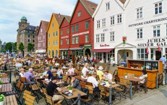 Open air restaurants and cafes in front of  the wooden Hanseatic merchants buildings of the Bryggen, an ancient fjordside wharf, now a major tourist attraction and UNESCO World Heritage Site, Bergen, Norway
