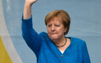 TOPSHOT - German Chancellor Angela Merkel waves as she stands on stage during a campaign rally for Christian Democratic Union CDU leader and chancellor candidate Armin Laschet (not pictured) in Aachen, western Germany, on September 25, 2021, one day ahead of the German federal elections. (Photo by Ina Fassbender / AFP)
